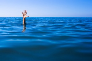 Help needed. Drowning man's hand in sea or ocean.